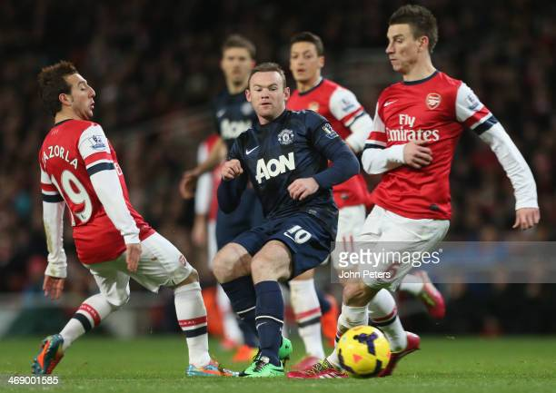 Wayne Rooney of Manchester United in action with Santi Cazorla and Laurent Koscielny of Arsenal during the Barclays Premier League match between...