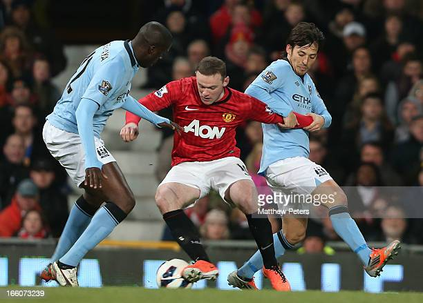 Wayne Rooney of Manchester United in action with Yaya Toure and David Silva of Manchester City during the Barclays Premier League match between...