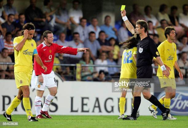 Wayne Rooney of Manchester United is booked by referee Kim Milton Neilson during the UEFA Champions League match between Villarreal and Manchester...
