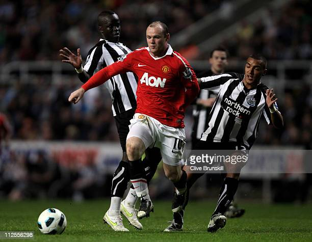 Wayne Rooney of Manchester United is challenged by Cheik Tiote and Danny Simpson of Newcastle United during the Barclays Premier League match between...