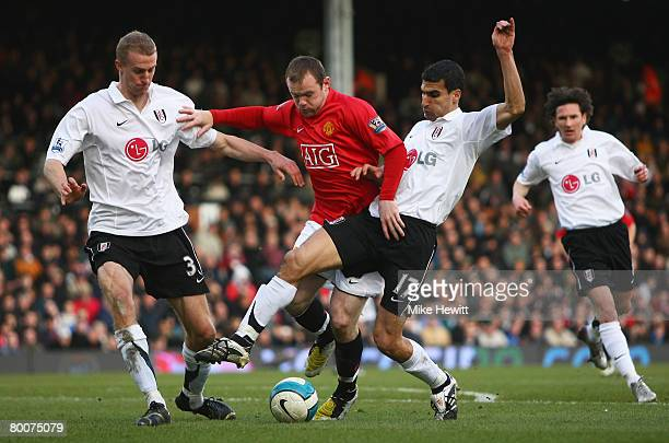 Wayne Rooney of Manchester United is challenged by Paul Stalteri and Brede Hangeland of Fulham during the Barclays Premier League match between...