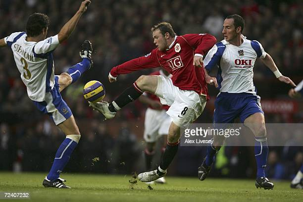 Wayne Rooney of Manchester United is challenged for the ball by Dejan Stefanovic and Andy O?Brien of Portsmouth during the Barclays Premiership match...