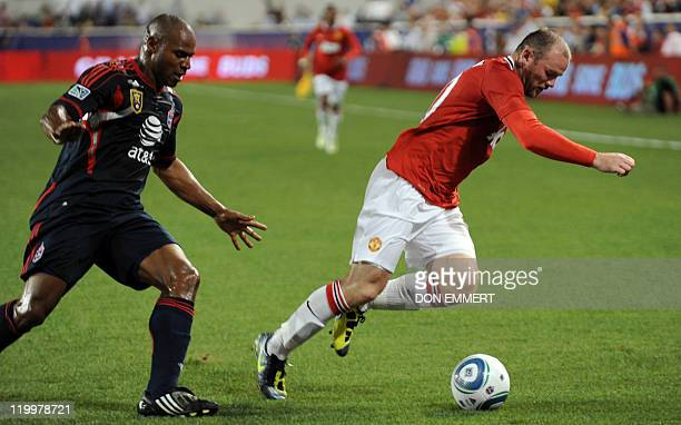 Wayne Rooney of Manchester United is defended by Jamison Olave of the MLS AllStars in the second half on July 27 2011 at Red Bull Arena in Harrison...