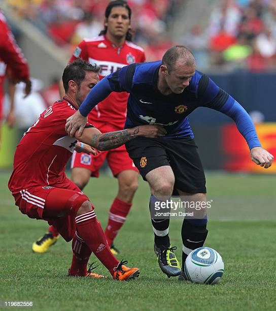 Wayne Rooney of Manchester United is held by Daniel Paladini of the Chicago Fire in a friendly match during the World Football Challenge 2011 at...