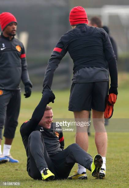 Wayne Rooney of Manchester United is helped off the ground by Michael Carrick after taking a fall during a training session at the Carrington...