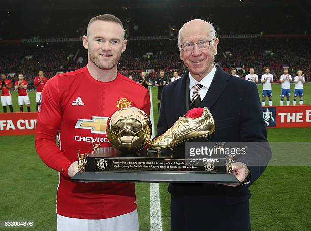 Wayne Rooney of Manchester United is presented with a golden boot by Sir Bobby Charlton to mark his 250th Manchester United goal which saw him break...