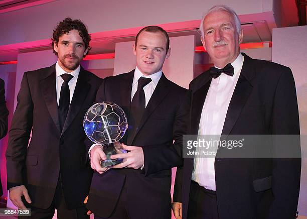 Wayne Rooney of Manchester United is presented with the Goal of the Season trophy by Owen Hargreaves and Alex Stepney during the club's annual Player...