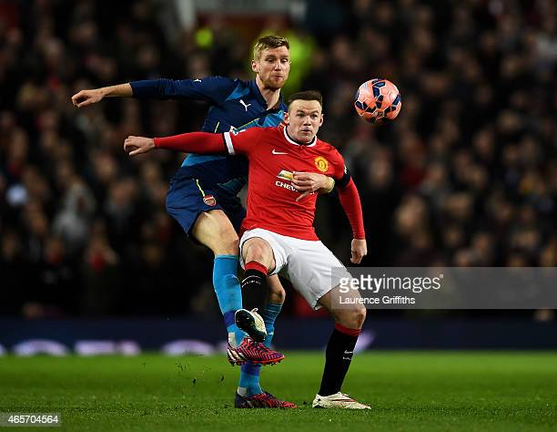 Wayne Rooney of Manchester United is tackled by Per Mertesacker of Arsenal during the FA Cup Quarter Final match between Manchester United and...