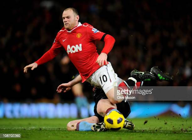 Wayne Rooney of Manchester United is tackled by Richard Dunne of Aston Villa during the Barclays Premier League match between Manchester United and...