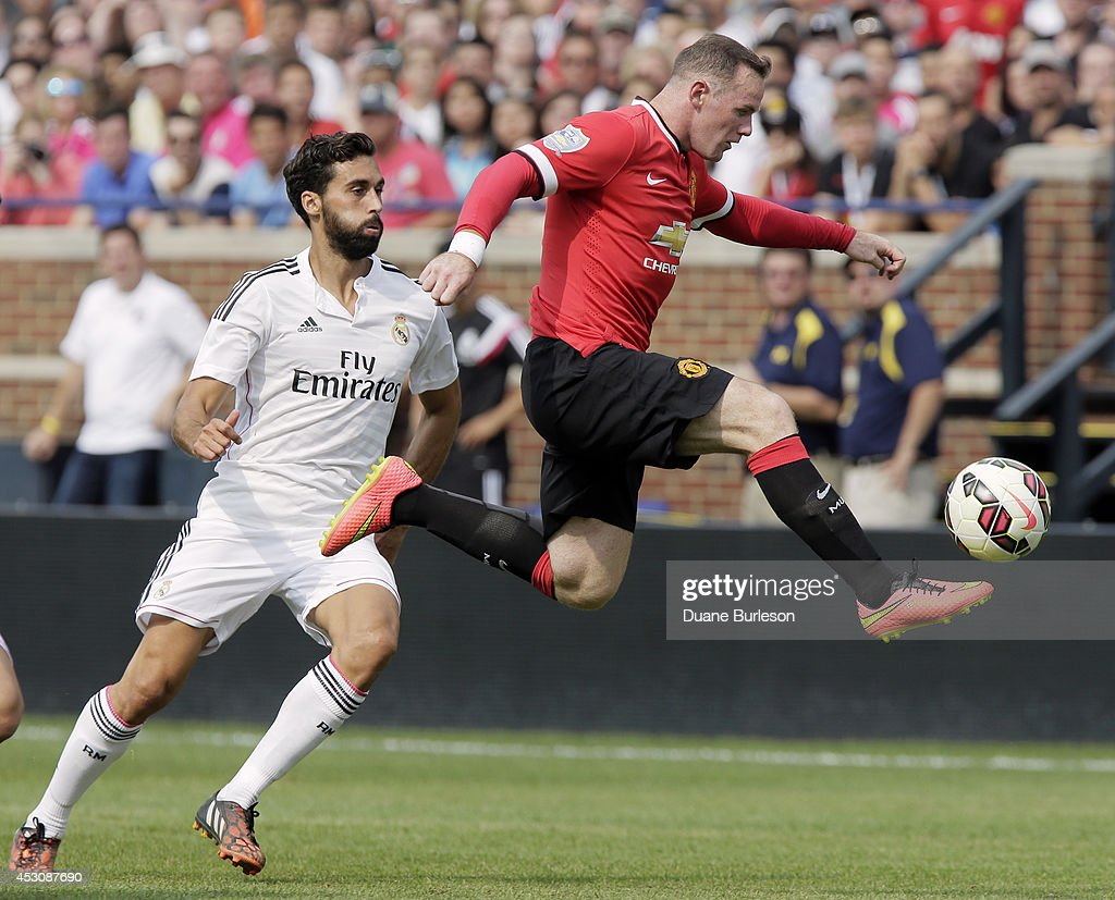 Wayne Rooney #10 of Manchester United kicks the ball away from Alvaro Arbeloa #17 of Real Madrid during the second half of the Guinness International Champions Cup at Michigan Stadium on August 2, 2014, in Ann Arbor, Mich