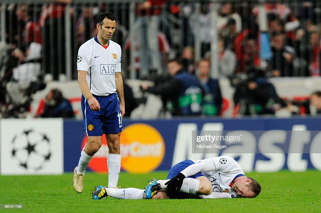 Wayne Rooney of Manchester United lies injured watched by Ryan Giggs during the UEFA Champions League quarter final first leg match between Bayern Muenchen and Manchester United at the Allianz Arena on March 30, 2010 in Munich, Germany.
