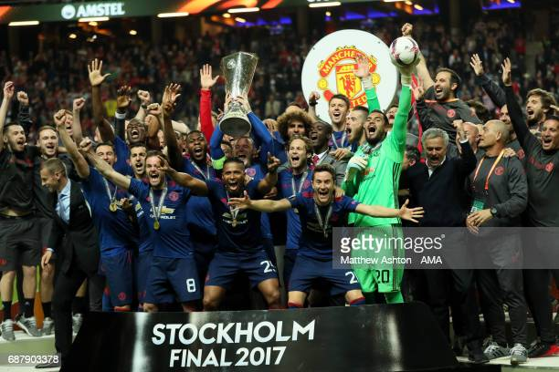 Wayne Rooney of Manchester United lifts the trophy as his teammates celebrate at the end of the UEFA Europa League Final between Ajax and Manchester...
