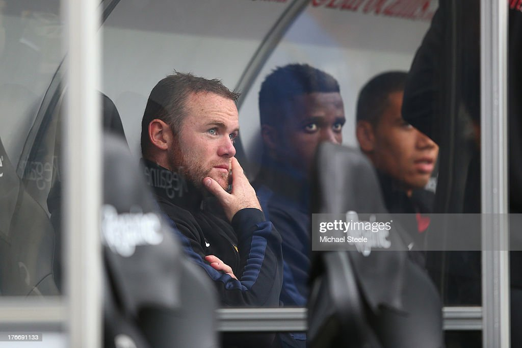 Wayne Rooney of Manchester United looks on from the bench during the Barclays Premier League match between Swansea City and Manchester United at the Liberty Stadium on August 17, 2013 in Swansea, Wales.