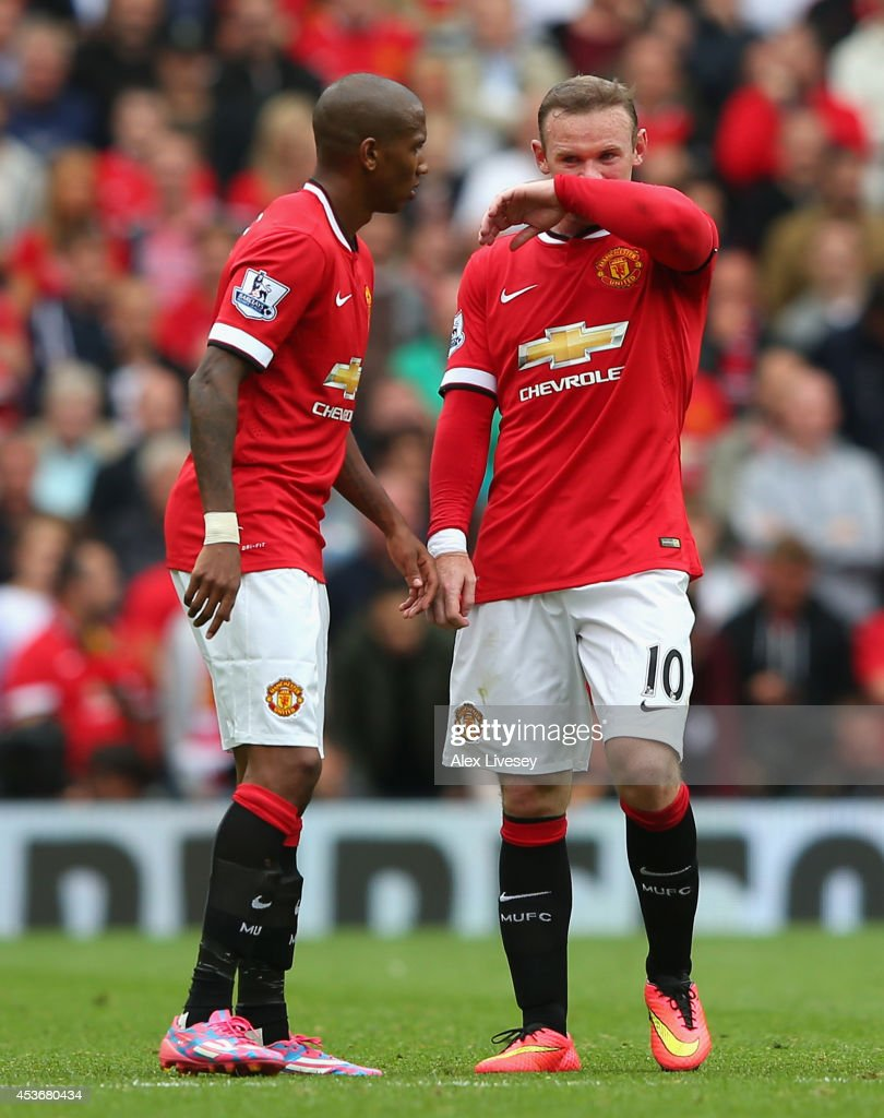 Wayne Rooney of Manchester United looks on with team-mate Ashley Young (L) during the Barclays Premier League match between Manchester United and Swansea City at Old Trafford on August 16, 2014 in Manchester, England.