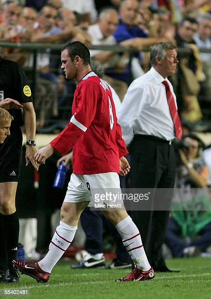 Wayne Rooney of Manchester United passes manager Sir Alex Ferguson after being sent off by referee Kim Nielsen during the UEFA Champions League Group...