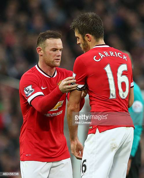 Wayne Rooney of Manchester United passes the Captain's armband to Michael Carrick during the Barclays Premier League match between Manchester United...