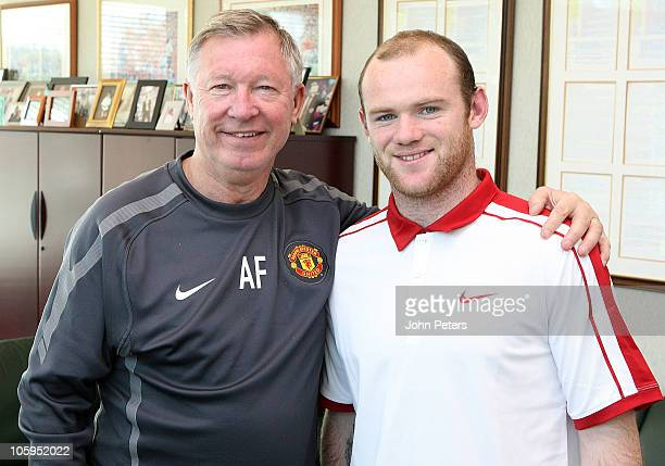 EQUIVALENT*** Wayne Rooney of Manchester United poses with manager Sir Alex Ferguson after signing a new fiveyear contract at the club at Carrington...