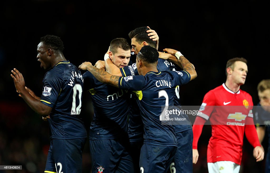 Wayne Rooney of Manchester United reacts as Southampton players celebrate victory after the Barclays Premier League match between Manchester United and Southampton at Old Trafford on January 11, 2015 in Manchester, England.