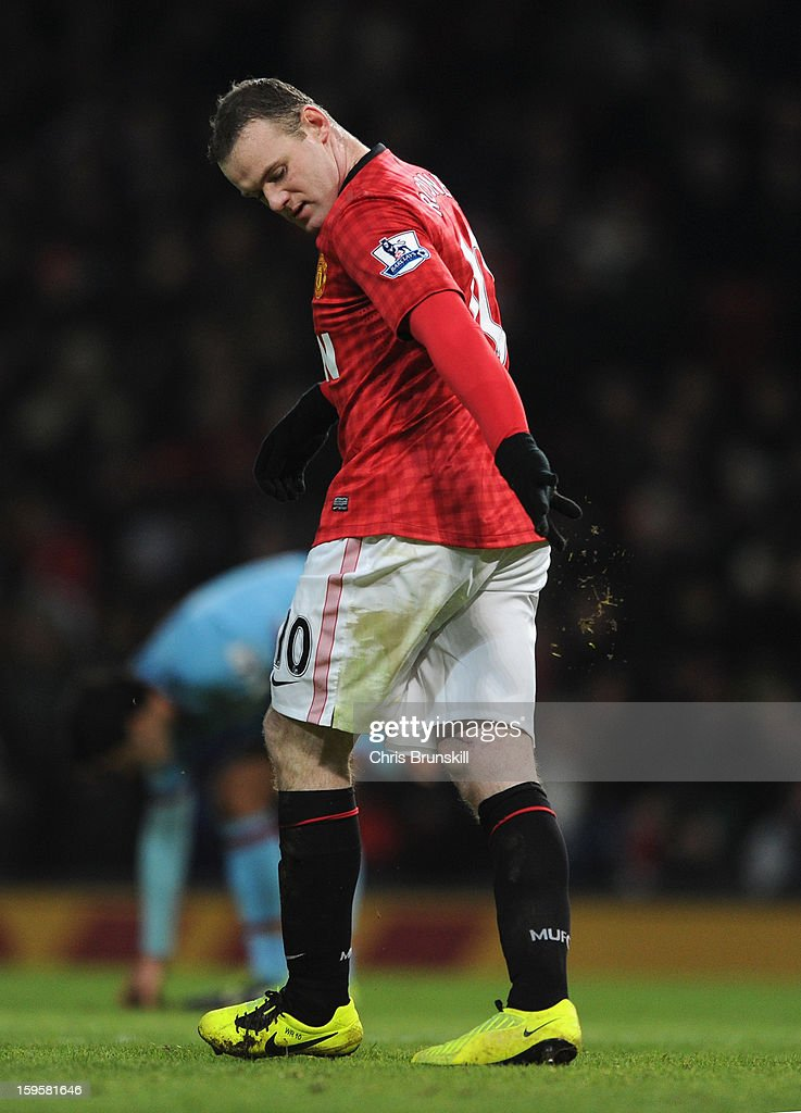 Wayne Rooney of Manchester United removes grass from his boots after missing a penalty kick during the FA Cup with Budweiser Third Round Replay match between Manchester United and West Ham United at Old Trafford on January 16, 2013 in Manchester, England.