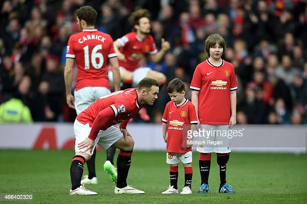 Wayne Rooney of Manchester United runs out onto the pitch with his son Kai who is a mascot for the day during the Barclays Premier League match...