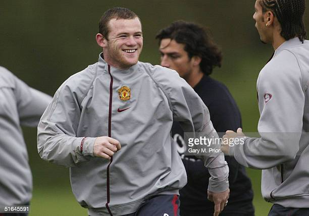 Wayne Rooney of Manchester United shares a joke with team mates during training prior to the Champions League match against Sparta Prague at The...