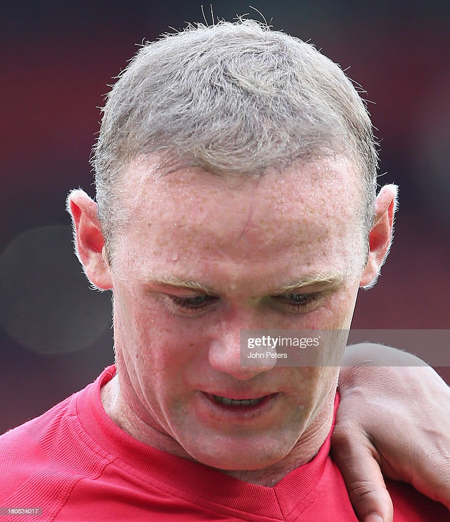 Wayne Rooney of Manchester United shows the scar on his forehead while walking off after the Barclays Premier League match between Manchester United and Crystal Palace at Old Trafford on September 14, 2013 in Manchester, England.