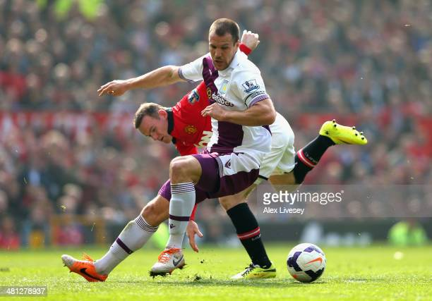 Wayne Rooney of Manchester United tangles with Ron Vlaar of Aston Villa during the Barclays Premier League match between Manchester United and Aston...