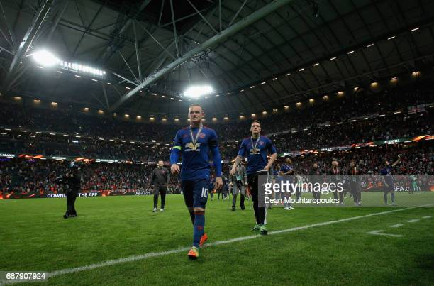 Wayne Rooney of Manchester United walks off the pitch with his winners medal after the UEFA Europa League Final between Ajax and Manchester United at...