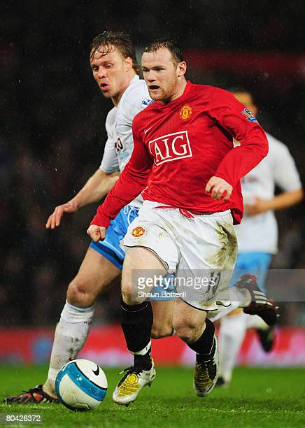 Wayne Rooney of ManUtd goes past Martin Laursen of Aston Villa to score his team's third goal during the Barclays Premier League match between...