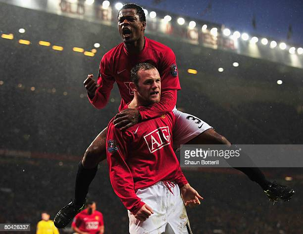 Wayne Rooney of ManUtd the scorer of his team's third goal is congratulated by teammate Patrice Evra during the Barclays Premier League match between...