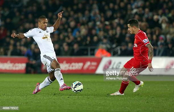 Wayne Routledge of Swansea attempts to pass the ball past Philippe Coutinho of Liverpool during the Premier League match between Swansea City and...