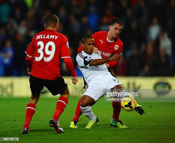 Wayne Routledge of Swansea battles with Andrew Taylor of Cardiff City during the Barclays Premier League match between Cardiff City and Swansea at...