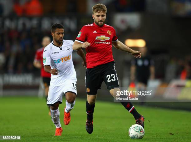 Wayne Routledge of Swansea City and Luke Shaw of Manchester United battle for possession during the Carabao Cup Fourth Round match between Swansea...