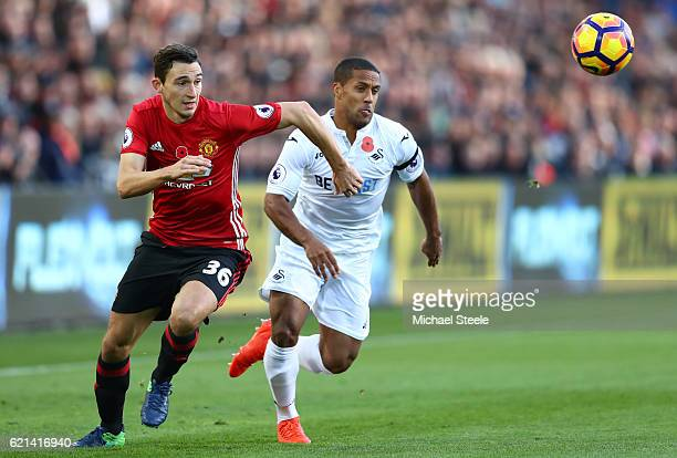 Wayne Routledge of Swansea City and Matteo Darmian of Manchester United chase the ball during the Premier League match between Swansea City and...