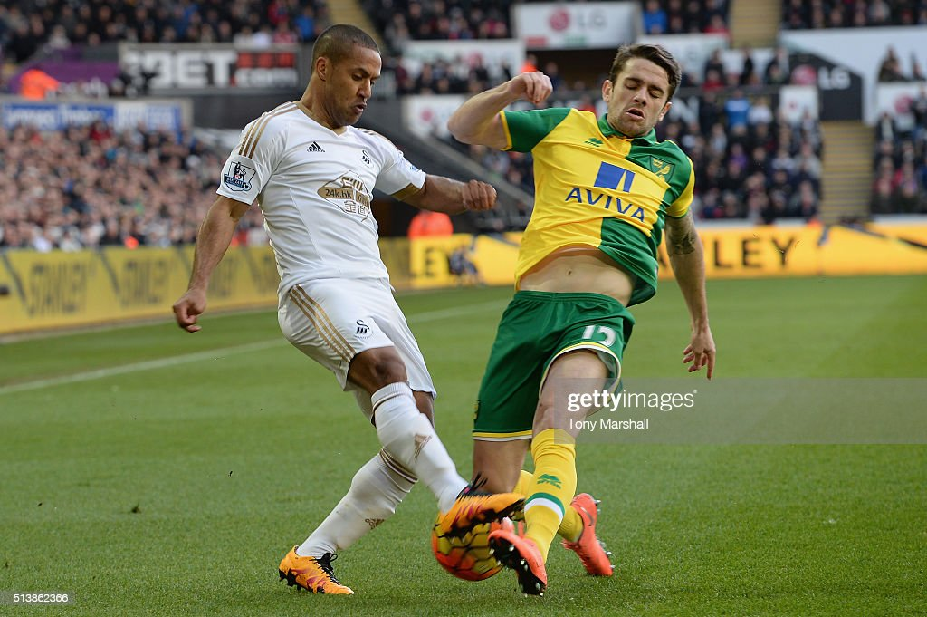 Wayne Routledge of Swansea City and Robbie Brady of Norwich City compete for the ball during the Barclays Premier League match between Swansea City and Norwich City at Liberty Stadium on March 5, 2016 in Swansea, Wales.