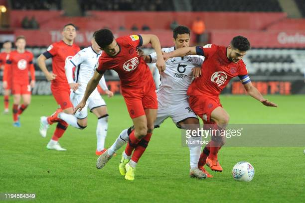 Wayne Routledge of Swansea City battle for possession with Antonee Robinson and Sam Morsy of Wigan Athletic during the Sky Bet Championship match...