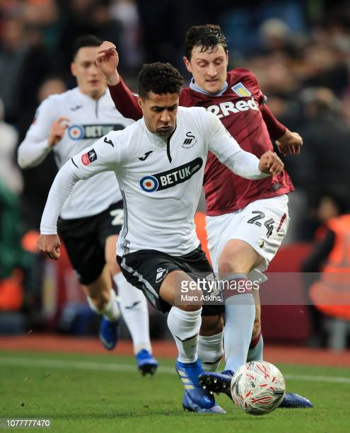 Wayne Routledge of Swansea City battles for possession with Tommy Elphick of Aston Villa during the FA Cup Third Round match between Aston Villa and...
