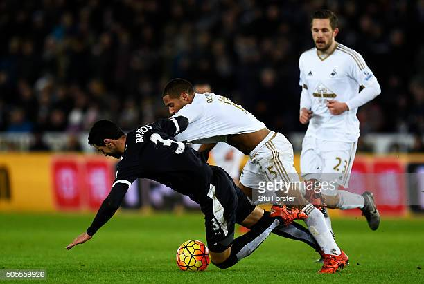 Wayne Routledge of Swansea City battles for the ball with Miguel Angel Britos of Watford during the Barclays Premier League match between Swansea...