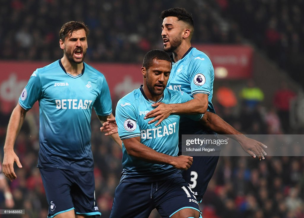 Wayne Routledge of Swansea City (C) celebrates with Fernando Llorente (L) and Neil Taylor (R) as he to scores their first goal during the Premier League match between Stoke City and Swansea City at Bet365 Stadium on October 31, 2016 in Stoke on Trent, England.