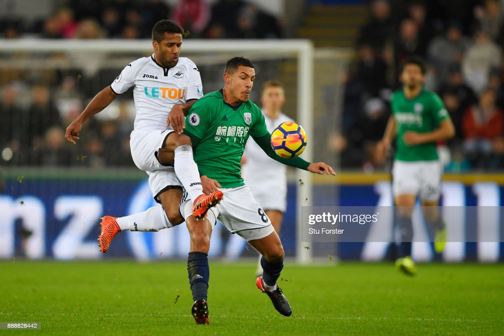 Wayne Routledge of Swansea City challenges Jake Livermore of West Bromwich Albion during the Premier League match between Swansea City and West Bromwich Albion at Liberty Stadium on December 9, 2017 in Swansea, Wales.