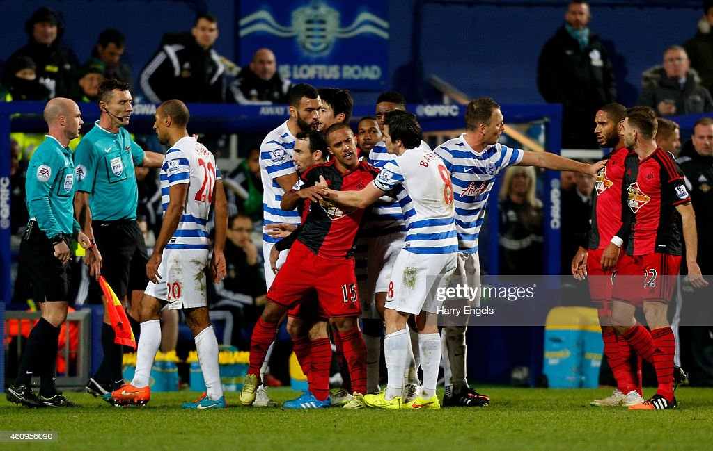 Wayne Routledge of Swansea City clashes with Joey Barton of QPR after fouling Karl Henry (L) of QPR during the Barclays Premier League match between Queens Park Rangers and Swansea City at Loftus Road on January 1, 2015 in London, England. Wayne Routledge of Swansea City was shown the red card forhischallenge on Karl Henry of QPR.