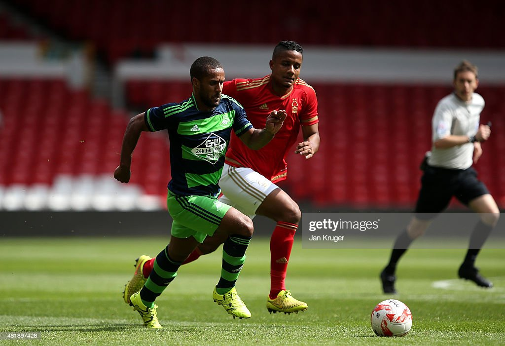 Wayne Routledge of Swansea City controls the ball from Michael Mancienne of Nottingham Forest during the pre season friendly match between Nottingham Forest and Swansea City at City Ground on July 25, 2015 in Nottingham, England.