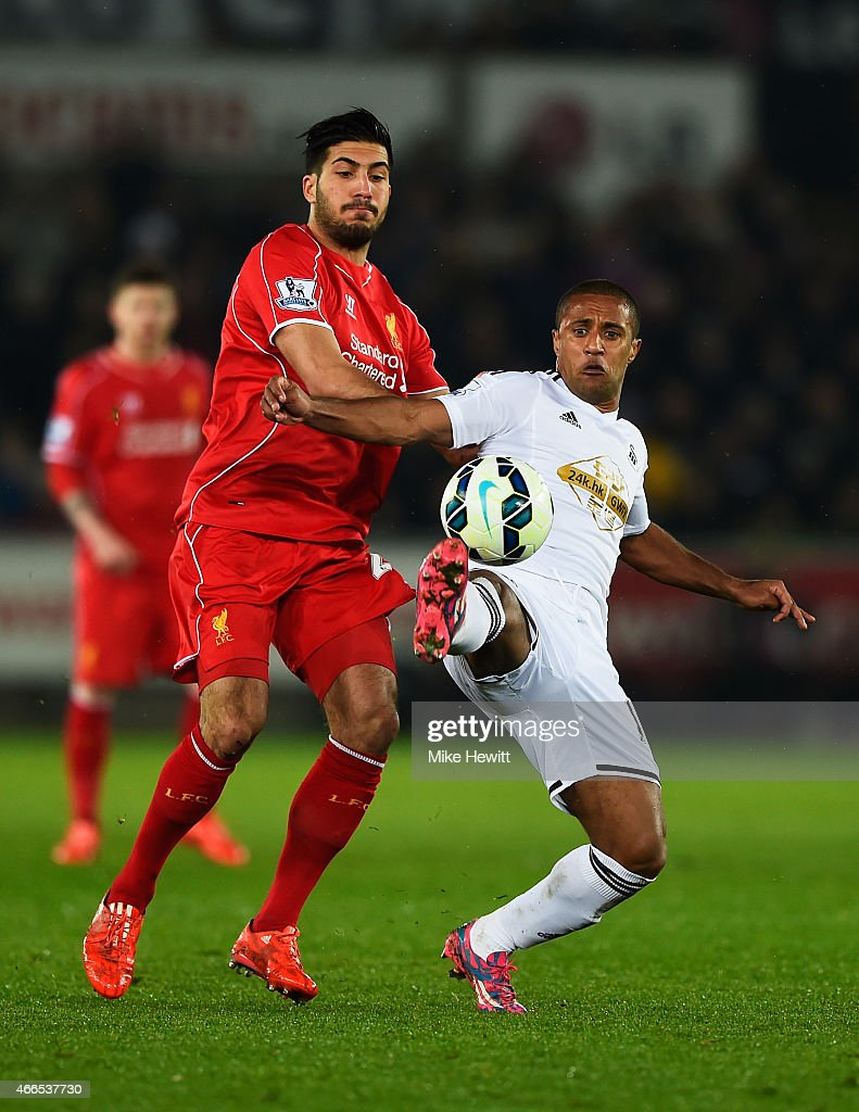 Wayne Routledge of Swansea City is challenged by Emre Can of Liverpool during the Barclays Premier League match between Swansea City and Liverpool at Liberty Stadium on March 16, 2015 in Swansea, Wales.