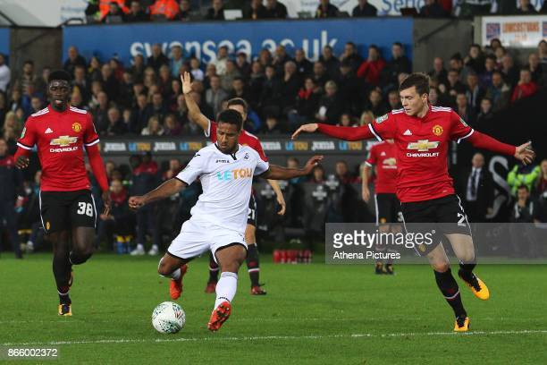 Wayne Routledge of Swansea City is challenged by Victor Lindelof of Manchester United during dthe Carabao Cup Fourth Round match between Swansea City...