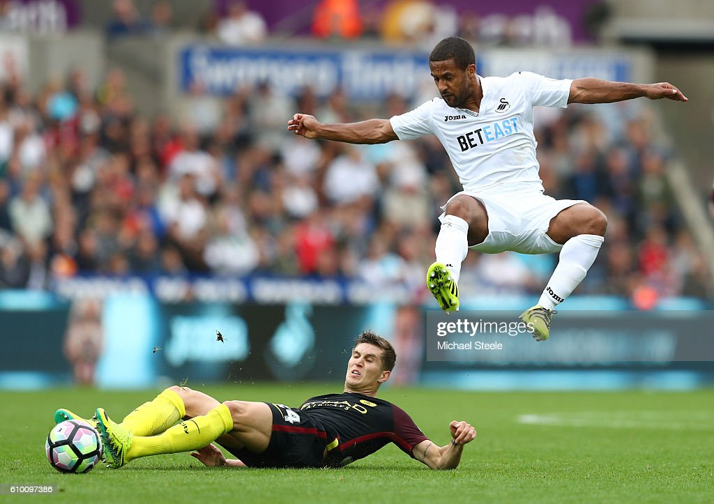 Wayne Routledge of Swansea City is fouled by John Stones of Manchester City during the Premier League match between Swansea City and Manchester City at the Liberty Stadium on September 24, 2016 in Swansea, Wales.
