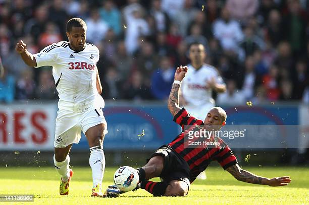 Wayne Routledge of Swansea City is tackled by Nigel De Jong of Manchester City during the Barclays Premier League match between Swansea City and...