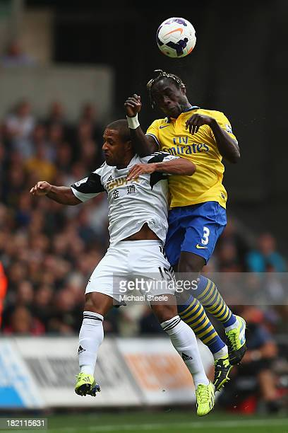 Wayne Routledge of Swansea City leaps with Bacary Sagna of Arsenal during the Barclays Premier League match between Swansea City and Arsenal at the...