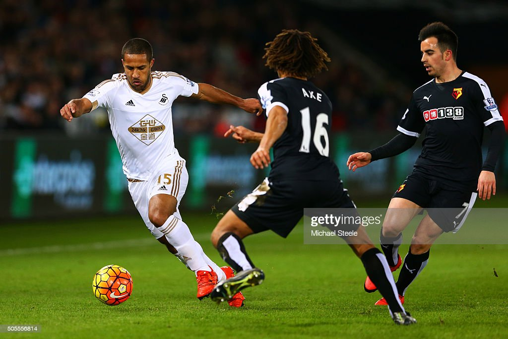 Wayne Routledge of Swansea City runs with the ball at Nathan Ake and Jose Manuel Jurado of Watford during the Barclays Premier League match between Swansea City and Watford at Liberty Stadium on January 18, 2016 in Swansea, Wales.