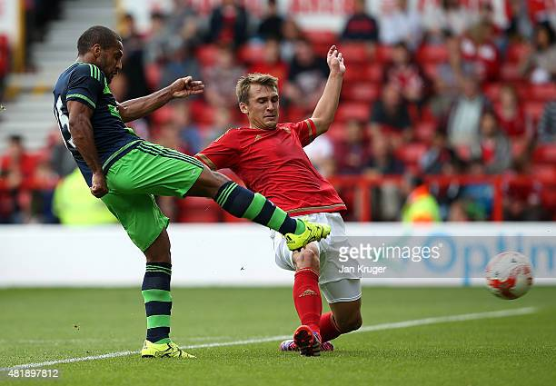 Wayne Routledge of Swansea City shoots at goal under pressure from Matt Mills of Nottingham Forest during the pre season friendly match between...