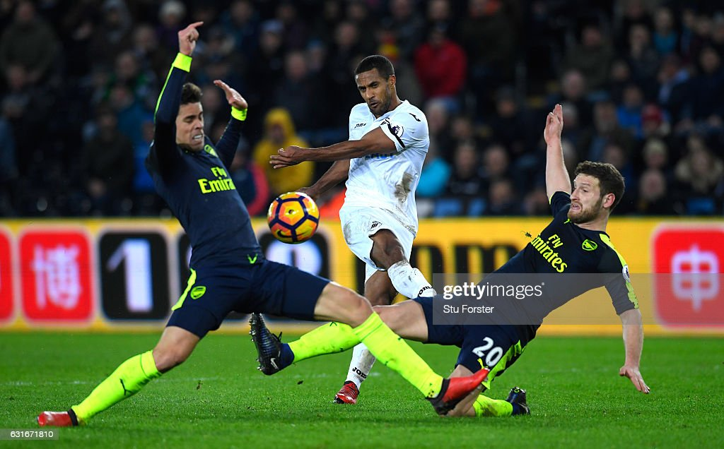 Wayne Routledge of Swansea City shoots, while Gabriel of Arsenal (L) and Shkodran Mustafi of Arsenal (R) block during the Premier League match between Swansea City and Arsenal at Liberty Stadium on January 14, 2017 in Swansea, Wales.